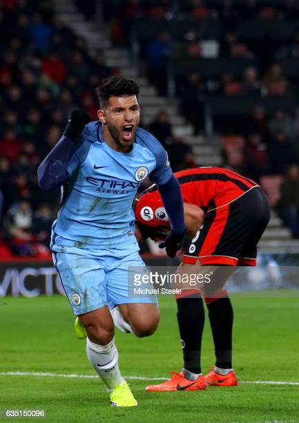 Sergio Aguero of Manchester City celebrates after sliding in next to Tyrone Mings of Bournemouth to score his team's second goal during the Premier...