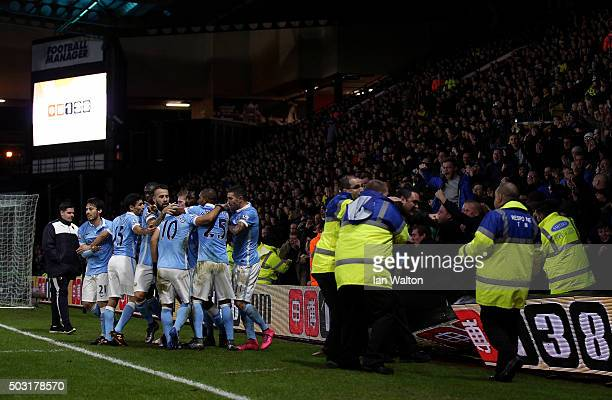 Sergio Aguero of Manchester City celebrates with his team mates as supporters fall onto the pitch during the Barclays Premier League match between...