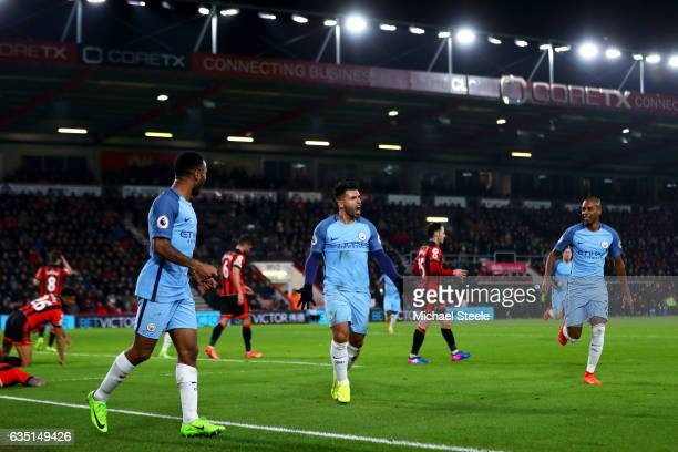 Sergio Aguero of Manchester City celebrates with Raheem Sterling and Fernandinho after sliding in next to Tyrone Mings of Bournemouth to score his...
