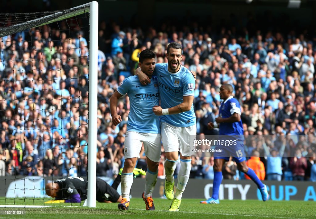 Sergio Aguero of Manchester City celebrates with teammate Alvaro Negredo (R) after scoring his team's third goal from the penalty spot during the Barclays Premier League match between Manchester City and Everton at Etihad Stadium on October 5, 2013 in Manchester, England.