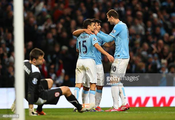 Sergio Aguero of Manchester City celebrates with teammates Jesus Navas and Edin Dzeko after scoring his team's fourth goal during the Barclays...