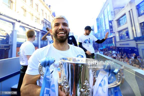 Sergio Aguero of Manchester City celebrates with the EFL Cup trophy on board a parade bus during the Manchester City Teams Celebration Parade on May...