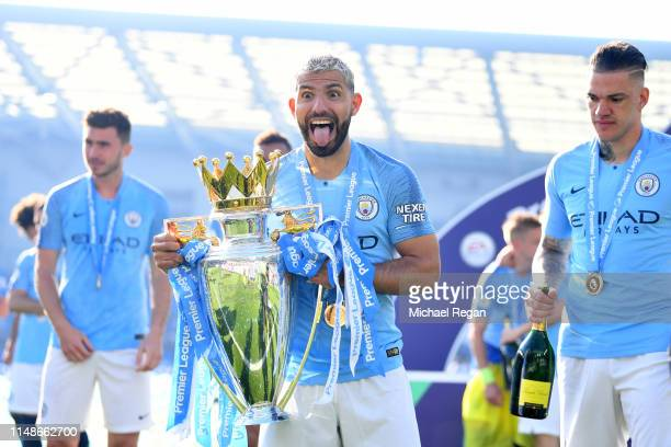 Sergio Aguero of Manchester City celebrates with the Premier League Trophy after winning the title following the Premier League match between...