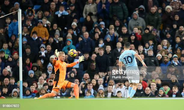 Sergio Aguero of Manchester City chips the ball over Kasper Schmeichel of Leicester City to make it 41 during the Premier League match between...