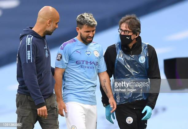 Sergio Aguero of Manchester City comes off the pitch injured as he speaks with Pep Guardiola, Manager of Manchester City during the Premier League...