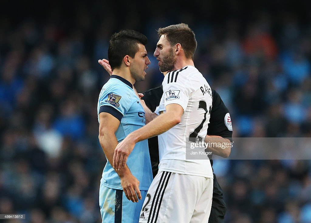 Sergio Aguero of Manchester City confronts Angel Rangel of Swansea City during the Barclays Premier League match between Manchester City and Swansea City at Etihad Stadium on November 22, 2014 in Manchester, England.