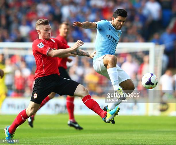 Sergio Aguero of Manchester City controls the ball under pressure from Aron Gunnarsson of Cardiff during the Barclays Premier League match between...