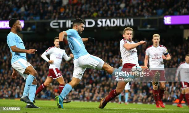 Sergio Aguero of Manchester City crosses the ball under pressure from Charlie Taylor of Burnley during The Emirates FA Cup Third Round match between...