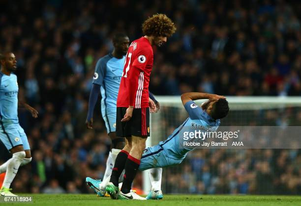 Sergio Aguero of Manchester City falls to the ground after clashing heads with Marouane Fellaini of Manchester United during the Premier League match...