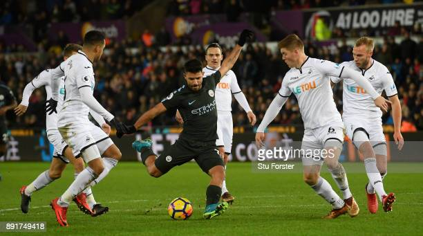 Sergio Aguero of Manchester City gets in a shot at goal despite the attentions of five Swansea players during the Premier League match between...