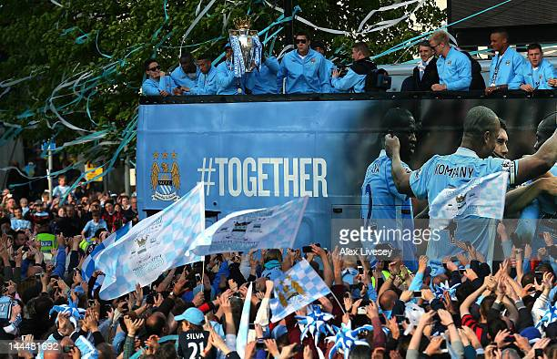 Sergio Aguero of Manchester City holds the Barclays Premier League trophy as the players of Manchester City leave Manchester Town Hall in an open top...