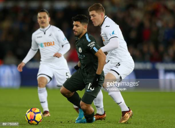 Sergio Aguero of Manchester City is challenged by Alfie Mawson of Swansea City during the Premier League match between Swansea City and Manchester...
