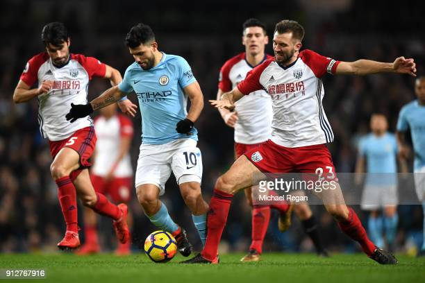 Sergio Aguero of Manchester City is challenged by Gareth McAuley of West Bromwich Albion and Claudio Yacob of West Bromwich Albion during the Premier...