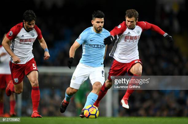 Sergio Aguero of Manchester City is challenged by Grzegorz Krychowiak of West Bromwich Albion during the Premier League match between Manchester City...