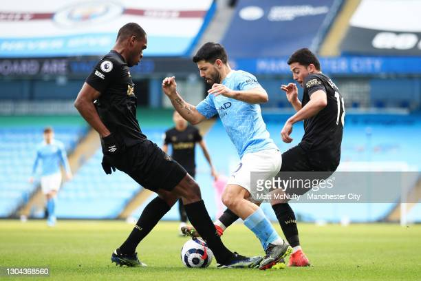 Sergio Aguero of Manchester City is challenged by Issa Diop and Pablo Fornals of West Ham United during the Premier League match between Manchester...