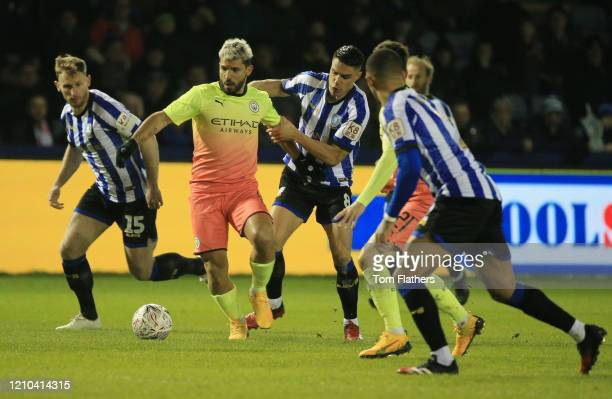 Sergio Aguero of Manchester City is challenged by Joey Pelupessy of Sheffield Wednesday during the FA Cup Fifth Round match between Sheffield...