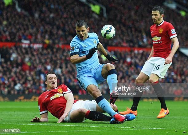 Sergio Aguero of Manchester City is challenged by Phil Jones of Manchester United during the Barclays Premier League match between Manchester United...