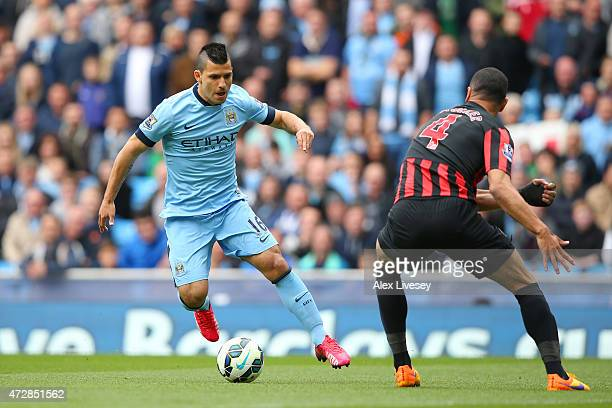 Sergio Aguero of Manchester City is challenged by Steven Caulker of QPR during the Barclays Premier League match between Manchester City and Queens...