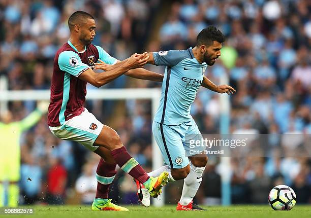 Sergio Aguero of Manchester City is challenged by Winston Reid of West Ham United during the Premier League match between Manchester City and West...