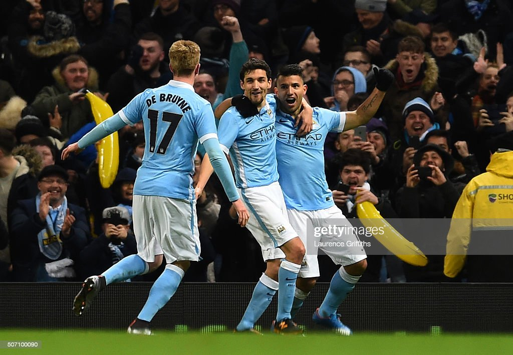 Sergio Aguero of Manchester City is congratulated by teammates David Silva and Kevin De Bruyne of Manchester City after scoring his team's third goal during the Capital One Cup Semi Final, second leg match between Manchester City and Everton at the Etihad Stadium on January 27, 2016 in Manchester, England.