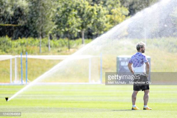 Sergio Aguero of Manchester City is cooled down by one of the sprinklers during the training session at Manchester City Football Academy on June 01...