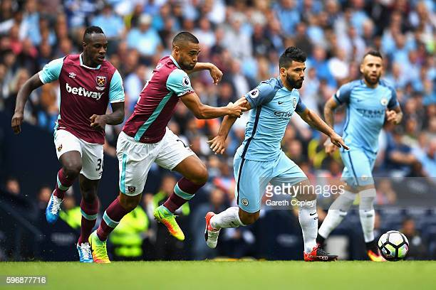 Sergio Aguero of Manchester City is held by Winston Reid of West Ham United during the Premier League match between Manchester City and West Ham...
