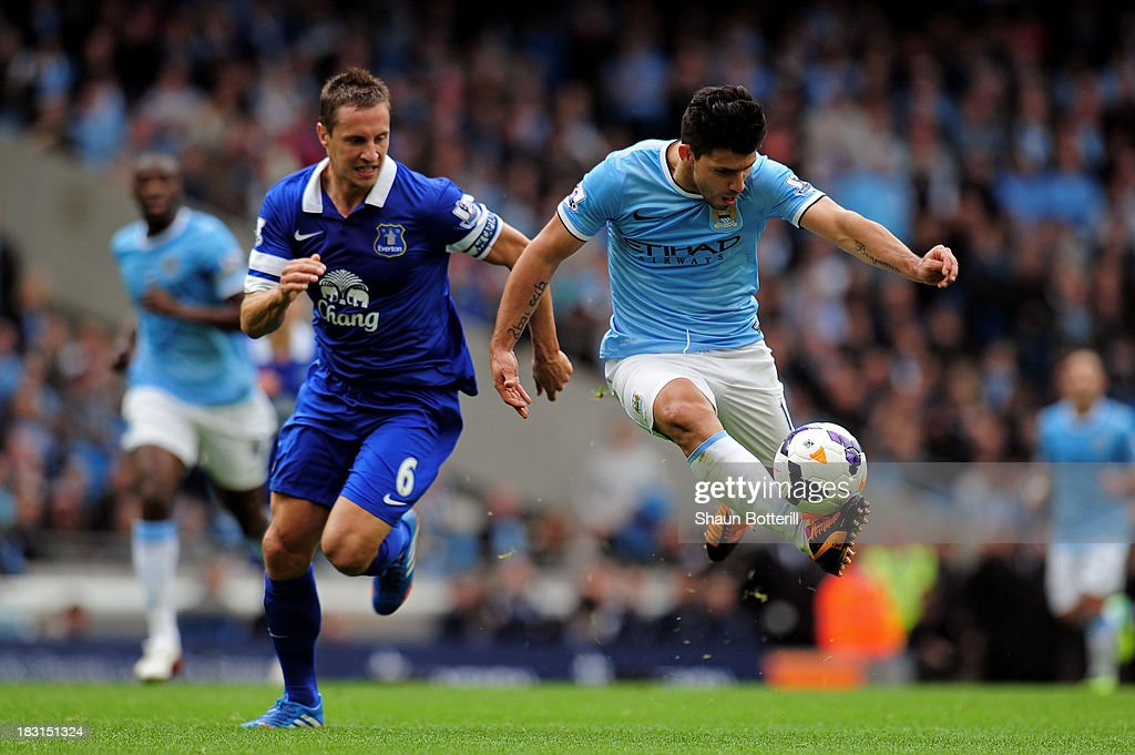 Sergio Aguero of Manchester City is pursued by Phil Jagielka of Everton during the Barclays Premier League match between Manchester City and Everton at Etihad Stadium on October 5, 2013 in Manchester, England.