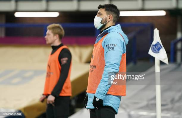 Sergio Aguero of Manchester City is seen wearing a face mask as he warms up at the side of the pitch during the Premier League match between Everton...