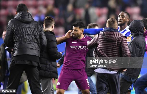 Sergio Aguero of Manchester City is surrounded by fans as he attempts to leave the pitch after the Emirates FA Cup Fifth Round match between Wigan...