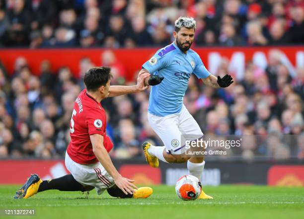 Sergio Aguero of Manchester City is tackled by Harry Maguire of Manchester United during the Premier League match between Manchester United and...