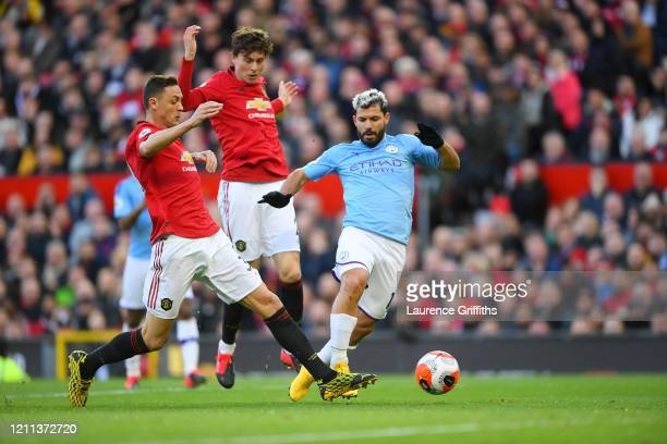Sergio Aguero of Manchester City is tackled by Nemaja Matic and Victor Lindelof of Manchester United during the Premier League match between...