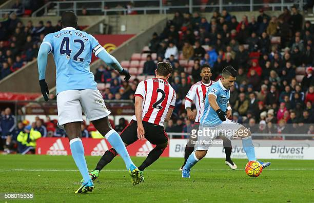 Sergio Aguero of Manchester City runs past Billy Jones of Sunderland to score his team's first goal during the Barclays Premier League match between...