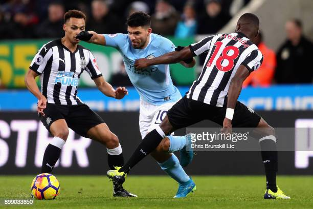 Sergio Aguero of Manchester City runs past Jacob Murphy and Chancel Mbemba both of Newcastle United during the Premier League match between Newcastle...
