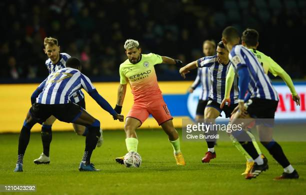 Sergio Aguero of Manchester City runs with the ball under pressure from Dominic Iorfa of Sheffield Wednesday during the FA Cup Fifth Round match...
