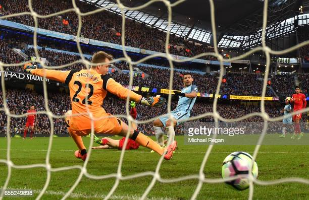 Sergio Aguero of Manchester City scores his sides first goal past Simon Mignolet of Liverpool during the Premier League match between Manchester City...