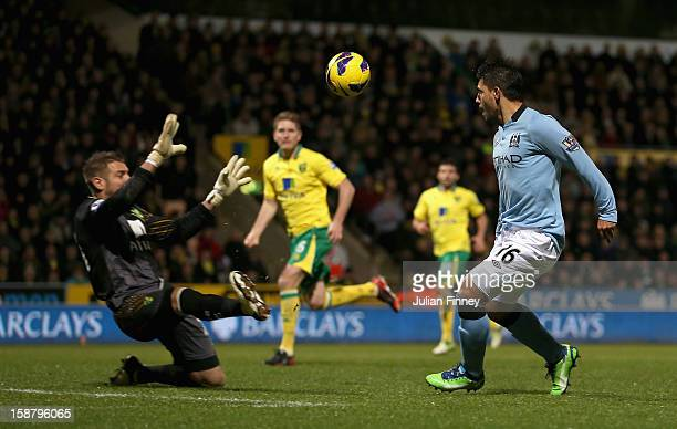 Sergio Aguero of Manchester City scores his side's third goal past Mark Bunn of Norwich City during the Barclays Premier League match between Norwich...