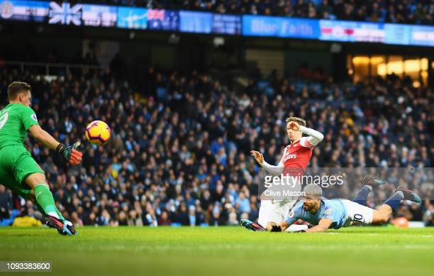 Sergio Aguero of Manchester City scores his team's first goal as Bernd Leno and Nacho Monreal of Arsenal challenge during the Premier League match...
