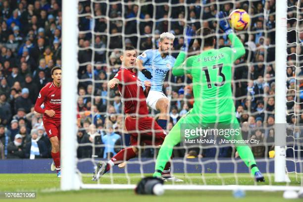 Sergio Aguero of Manchester City scores his team's first goal past Alisson of Liverpool during the Premier League match between Manchester City and...