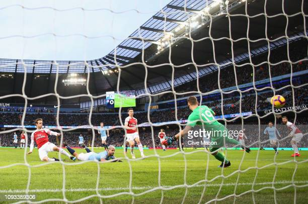 Sergio Aguero of Manchester City scores his team's first goal past Bernd Leno as Nacho Monreal of Arsenal challenges during the Premier League match...