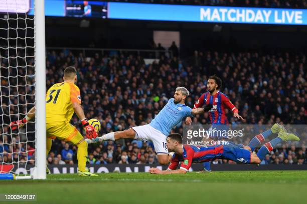 Sergio Aguero of Manchester City scores his team's first goal past Vicente Guaita and Luka Milivojevic of Crystal Palace during the Premier League...
