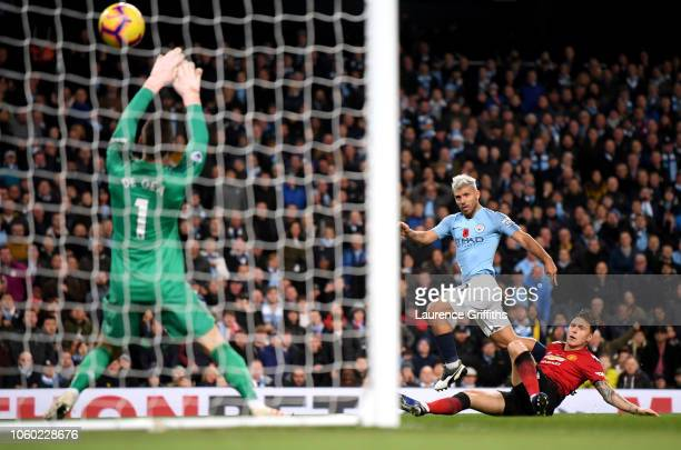 Sergio Aguero of Manchester City scores his team's second goal past David De Gea of Manchester United while being challenged by Victor Lindelof of...