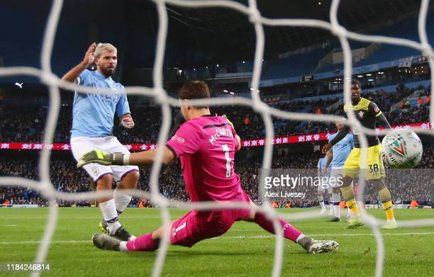 Sergio Aguero of Manchester City scores his team's third goal past Alex McCarthy of Southampton during the Carabao Cup Round of 16 match between...