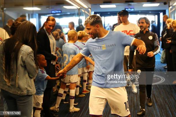 Sergio Aguero of Manchester City shakes hands with a mascot in the tunnel at half time during the Premier League match between Manchester City and...