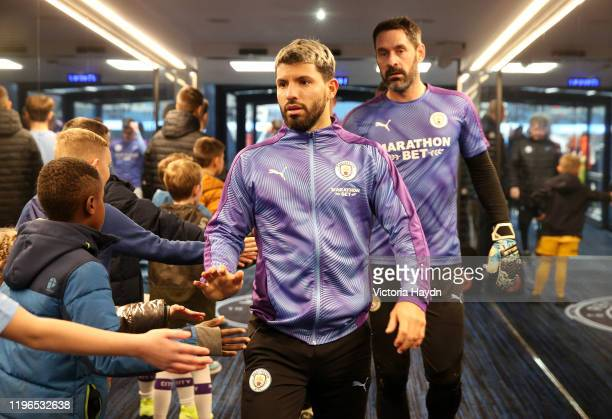 Sergio Aguero of Manchester City shakes hands with mascots after the teams warm up ahead of the Premier League match between Manchester City and...