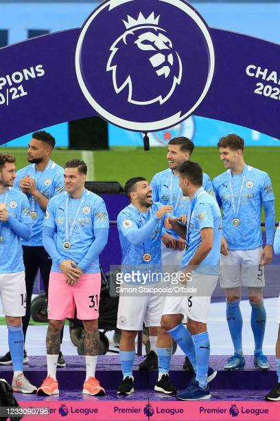 Sergio Aguero of Manchester City shares a joke with teammate Rodri of Manchester City during the post-match presentation after the Premier League...