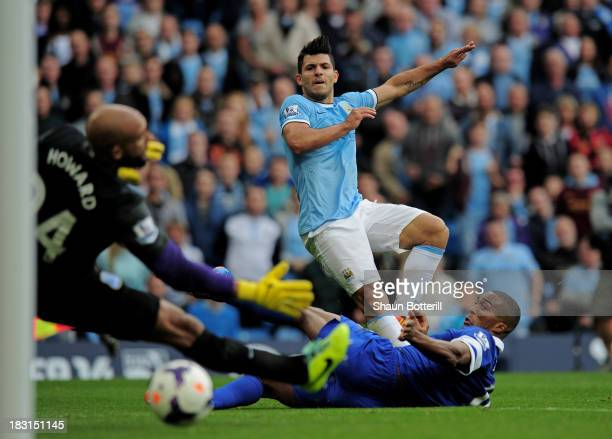 Sergio Aguero of Manchester City shoots past Sylvain Distin and Tim Howard of Everton to score his team's second goal during the Barclays Premier...