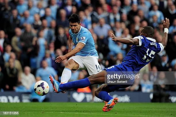 Sergio Aguero of Manchester City shoots past Sylvain Distin of Everton to score his team's second goal during the Barclays Premier League match...