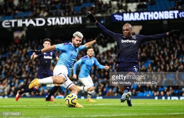Sergio Aguero of Manchester City shoots under pressure from Angelo Ogbonna of West Ham during the Premier League match between Manchester City and...
