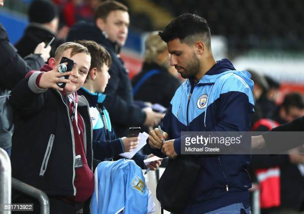 Sergio Aguero of Manchester City signs autographs as he arrives prior to the Premier League match between Swansea City and Manchester City at Liberty...