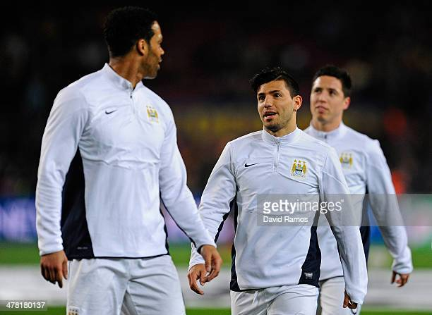 Sergio Aguero of Manchester City speaks with teammate Joleon Lescott whilst warming up prior to kickoff during the UEFA Champions League Round of 16,...